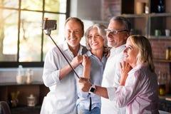 2 пожилых пары принимая фото в кухне Стоковая Фотография