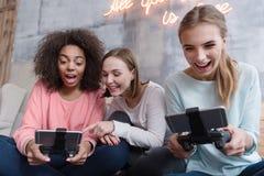 Позабавленные девушки держа консоли игры и играя игры Стоковые Фотографии RF