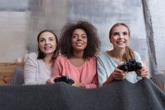 Позабавленные маленькие девочки играя игры в спальне дома Стоковая Фотография