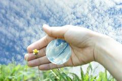 Позаботьте голубые мир и природа с человеческой рукой Стоковое Изображение