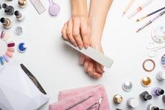позаботьте ноготь ногтя хлопка извлекая политуру пробирки красивые руки женщин делая ногти покрашенные с розовым нежным маникюром стоковое изображение