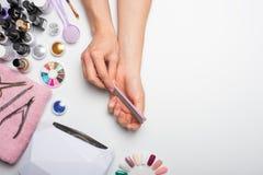 позаботьте ноготь ногтя хлопка извлекая политуру пробирки красивые руки женщин делая ногти покрашенные с розовым нежным маникюром стоковое фото rf