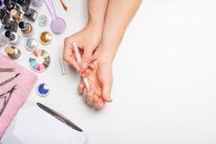 позаботьте ноготь ногтя хлопка извлекая политуру пробирки красивые руки женщин делая ногти покрашенные с розовым нежным маникюром стоковое фото