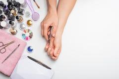 позаботьте ноготь ногтя хлопка извлекая политуру пробирки красивые руки женщин делая ногти покрашенные с розовым нежным маникюром стоковая фотография
