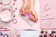позаботьте ноготь ногтя хлопка извлекая политуру пробирки красивые руки женщин делая ногти покрашенные с розовым нежным маникюром стоковое изображение rf