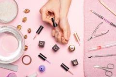 позаботьте ноготь ногтя хлопка извлекая политуру пробирки красивые руки женщин делая ногти покрашенные с розовым нежным маникюром стоковые изображения