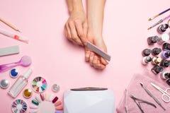 позаботьте ноготь ногтя хлопка извлекая политуру пробирки красивые руки женщин делая ногти покрашенные с розовым нежным маникюром стоковые изображения rf