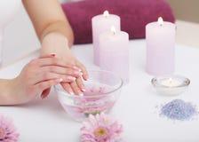 позаботьте ноготь ногтя хлопка извлекая политуру пробирки Крупный план красивых рук женщины с естественными ногтями i стоковая фотография