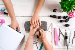 позаботьте ноготь ногтя хлопка извлекая политуру пробирки Крупный план женских рук храня ногти с профессиональной пилочкой для но стоковые фото