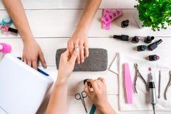 позаботьте ноготь ногтя хлопка извлекая политуру пробирки Крупный план женских рук храня ногти с профессиональной пилочкой для но стоковая фотография