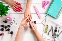 позаботьте ноготь ногтя хлопка извлекая политуру пробирки Крупный план женских рук храня ногти с профессиональной пилочкой для но стоковые изображения rf