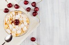 Позавтракайте с золотыми хлопьями мозоли, зрелой вишней, напудренным сахаром на белом деревянном взгляд сверху доски, космосе экз Стоковое Фото