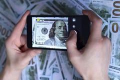 Позвоните по телефону в руке, изображении доллара, на предпосылке долларов Стоковые Фотографии RF