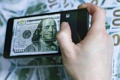Позвоните по телефону в руке, изображении доллара, на предпосылке долларов Стоковые Фото