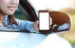 Позвоните по телефону в руке женщины показывая пустой экран сидя в автомобиле Стоковое Изображение RF