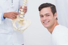 Позвоночник доктора объясняя анатомический к его пациенту Стоковые Фотографии RF