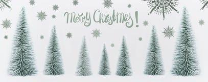 Поздравительная открытка веселого рождества с декоративным лесом елей и покрашенными снежинками стоковая фотография