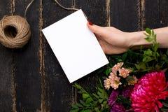 Поздравительная открытка в руке с букетом цветков на темной винтажной деревянной предпосылке стоковое фото rf