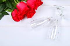 Поздравительная открытка дня валентинок, цветки красной розы, бокалы и подарочная коробка на деревянном столе Взгляд сверху Стоковое Фото