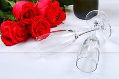 Поздравительная открытка дня валентинок, цветки красной розы, бокалы и подарочная коробка на деревянном столе Взгляд сверху Стоковое фото RF
