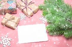 Поздравительная открытка Нового Года или рождества на розовой таблице с украшениями, елью рождества и подарками с космосом экземп стоковые изображения rf
