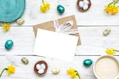 Поздравительная открытка пасхи в рамке сделанной из яичек триперсток, чашки капучино и весны цветет на белой деревянной предпосыл Стоковое Изображение RF