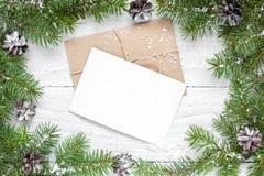 Поздравительная открытка рождества в рамке сделанной ветвей ели и конусов сосны Стоковое Изображение