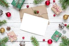 Поздравительная открытка рождества пустая в рамке сделанной из ветвей ели, красных ягод, украшений и подарочных коробок Стоковое Изображение