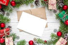 Поздравительная открытка рождества пустая в рамке сделанной из ветвей ели, красных украшений и подарочных коробок Стоковое фото RF