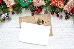 Поздравительная открытка рождества пустая с ветвями ели, украшениями, красными ягодами, подарочными коробками и конусами Стоковые Фото
