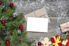Поздравительная открытка рождества с ветвями, украшениями и подарочными коробками ели над деревенской деревянной предпосылкой Стоковые Фото