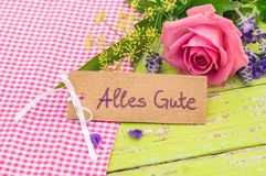 Поздравительная открытка с немецким текстом, Alles Gute, наилучшими пожеланиями середин и романтичным розовым букетом цветка Стоковое Фото