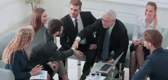 Поздравления! 2 жизнерадостных бизнесмена тряся руки пока Стоковые Фотографии RF