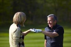 поздравляющ игроков в гольф укомплектуйте личным составом женщину стоковое фото