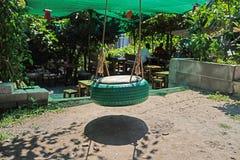 Позеленейте покрашенную смертную казнь через повешение качания автошины в парке с запачканной предпосылкой стоковое фото rf