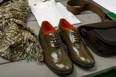 Позеленейте отлакированные ботинки Оксфорда около белых рубашки, сумки и шарфа на деревянной предпосылке задний взгляд Стоковая Фотография