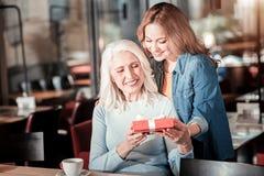 Позитв постарел женщина получая симпатичный настоящий момент от ее внимательной внучки Стоковая Фотография
