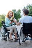 Позитв wheelchaired женщина получая цветки от ее заботя супруга инвалидов Стоковые Фото