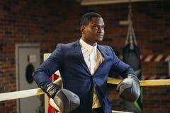 Позиция африканского бизнесмена стоящая в перчатках бокса стоковое фото
