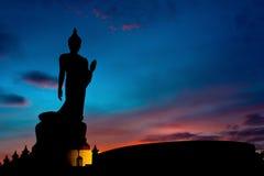 Позиция идя буддийской статуи в Twilight силуэте стоковое фото rf