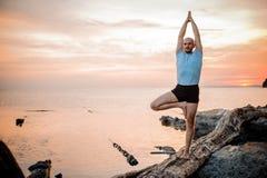 Позиция йоги на заходе солнца человеком стоковая фотография