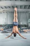 Позиция уравновешения акробатики кавказского человека гимнастическая на предпосылке спортзала стоковые изображения