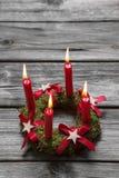 Поздравительная открытка: 4 красных горящих свечи пришествия на деревянном сером ба Стоковая Фотография RF