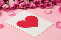 Поздравительная открытка дня ` s валентинки с розовыми цветками над розовым backgr Стоковая Фотография