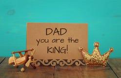 поздравительная открытка, плоская игрушка и король яркого блеска увенчивают Father& x27; концепция дня s Стоковое Фото