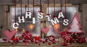 Поздравительная открытка рождества в красной, деревянном, свечах и с текстом стоковые изображения