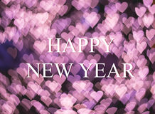Поздравительная открытка рождества и Нового Года на розовом сердце освещает bokeh Стоковые Изображения RF