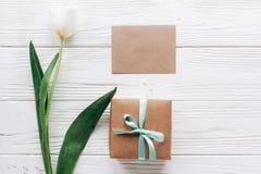 Поздравительная открытка с стильными присутствующими коробкой и тюльпанами на белом woode Стоковое Изображение RF