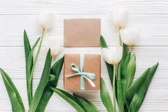 Поздравительная открытка с стильными присутствующими коробкой и тюльпанами на белом woode Стоковая Фотография RF