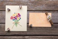 Поздравительная открытка с цветками на деревянной предпосылке Стоковые Изображения RF
